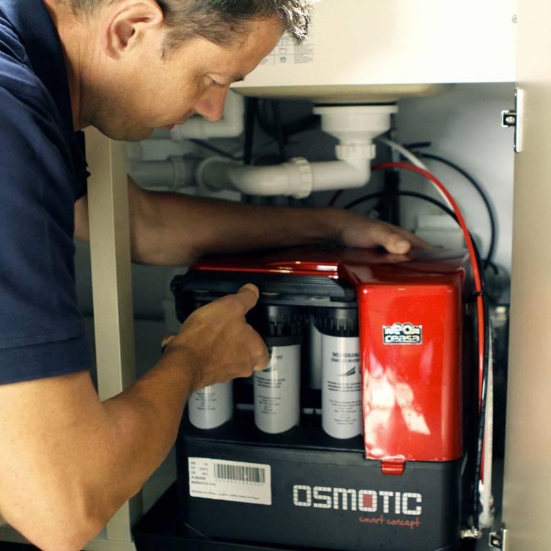 Installation sous l'évier du système Osmotic de Natarys pour filtrer l'eau du robinet par charbon actif et osmose inverse